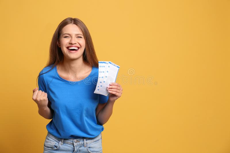 Portrait of happy young woman with lottery tickets on background, space for text royalty free stock photos