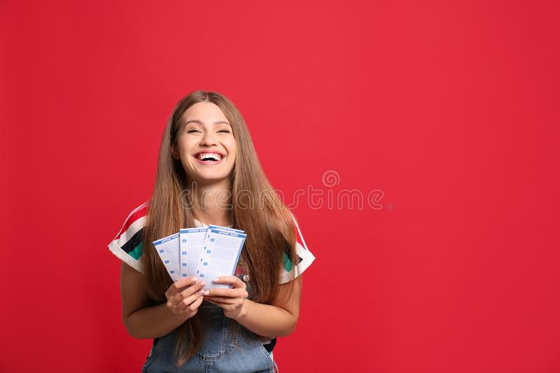 Portrait of happy young woman with lottery tickets on background stock photography