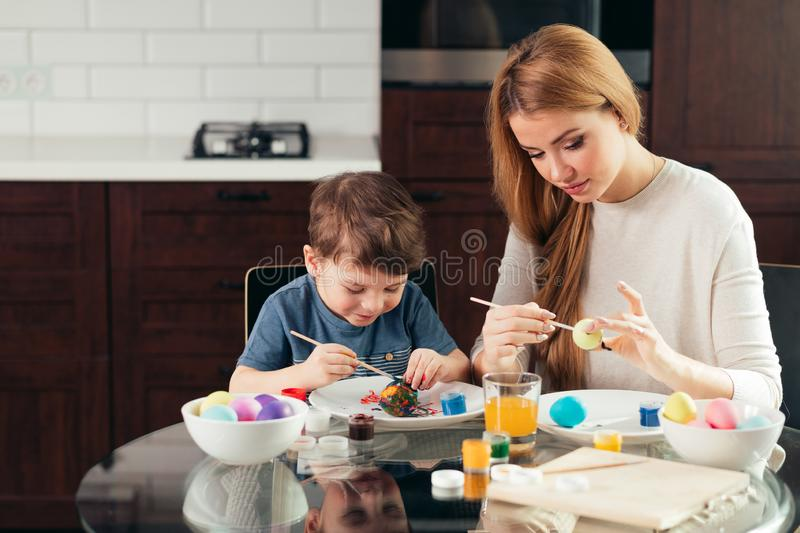 Portrait of happy young woman painting Easter eggs with her adorable little son royalty free stock photo