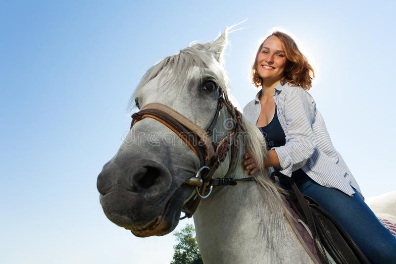 Portrait of happy young woman riding white horse royalty free stock image