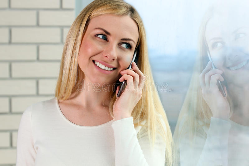 Portrait of happy young Woman Talking On Mobile Phone, standing near with window stock images