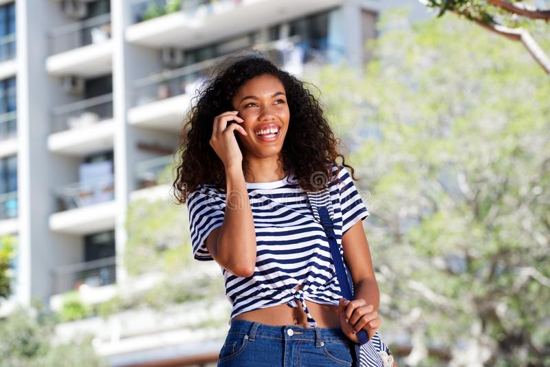 Happy young woman walking and talking on mobile phone outside stock photography