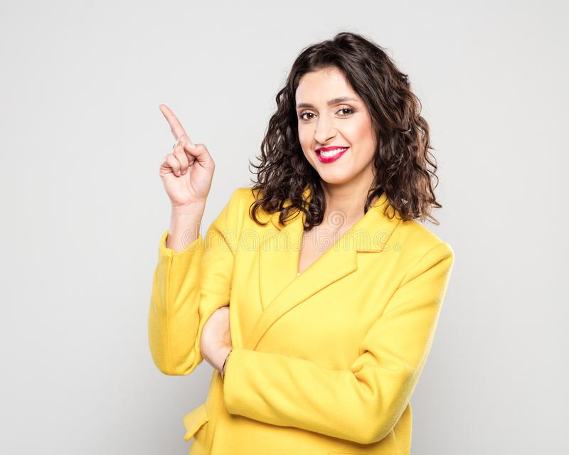 Portrait of happy young woman in yellow jacket pointing at copy stock photography