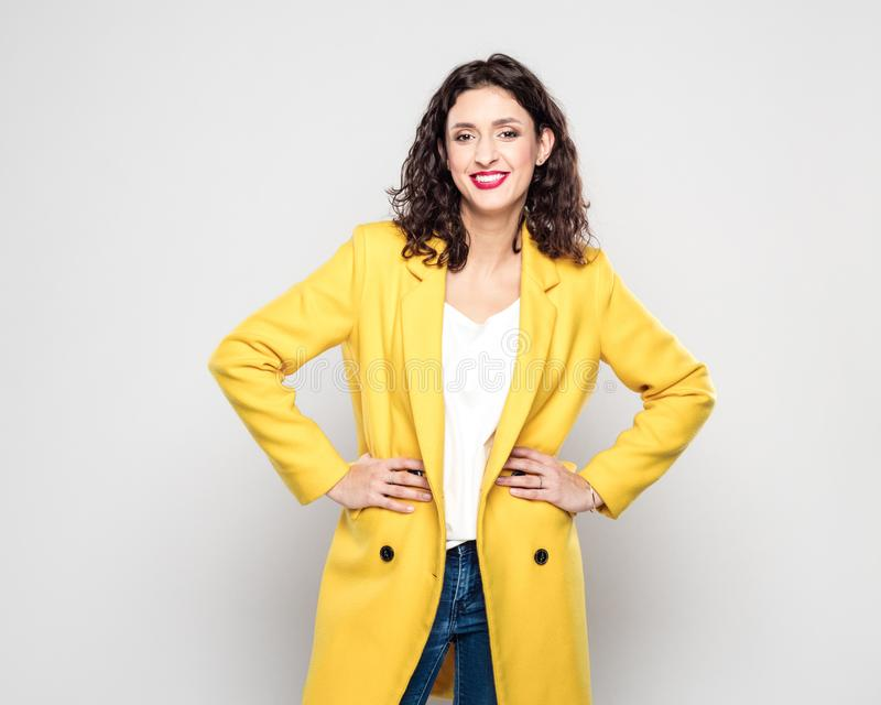 Portrait of happy young woman in yellow jacket royalty free stock images