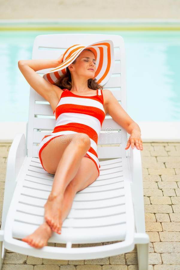 Portrait of happy young womanlaying on sunbed. Portrait of happy young woman in hat laying on sunbed royalty free stock photography