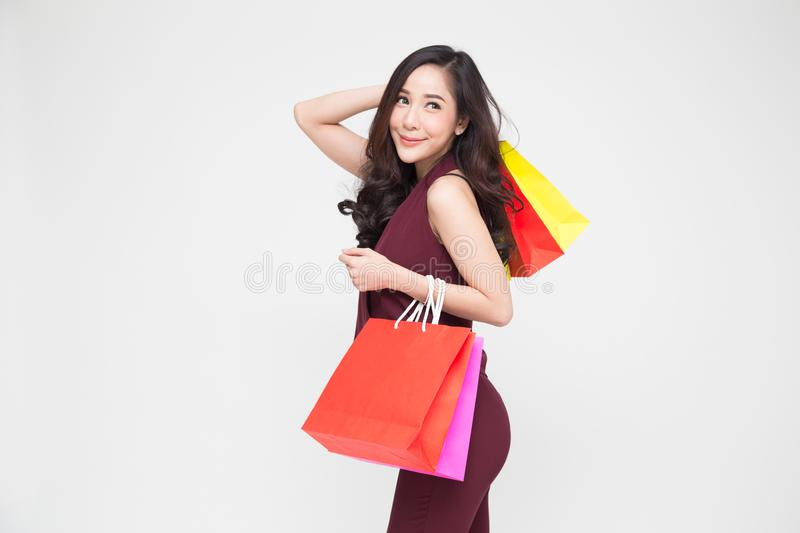 Portrait of a happy young women in red dress holding shopping bags isolated over white background, royalty free stock images