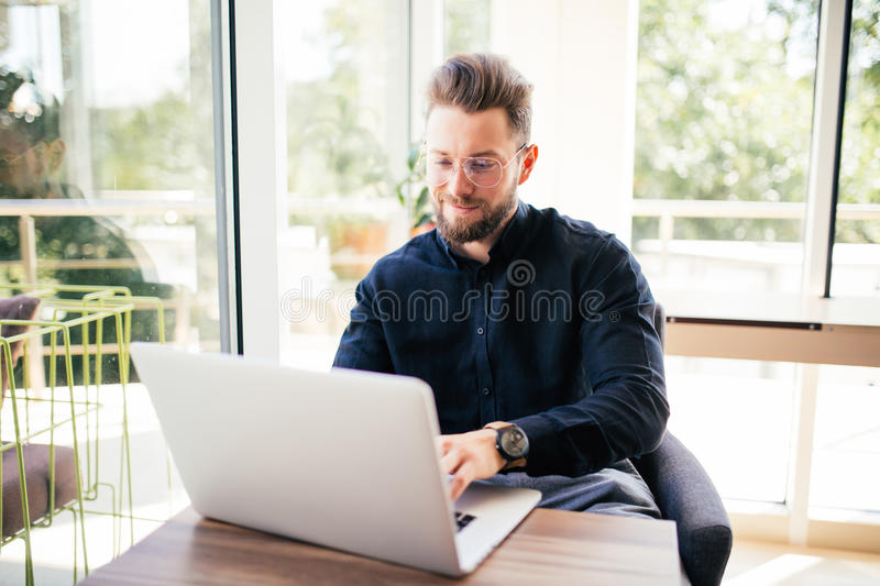 Portrait of happy young writer typing new book on laptop in office royalty free stock image
