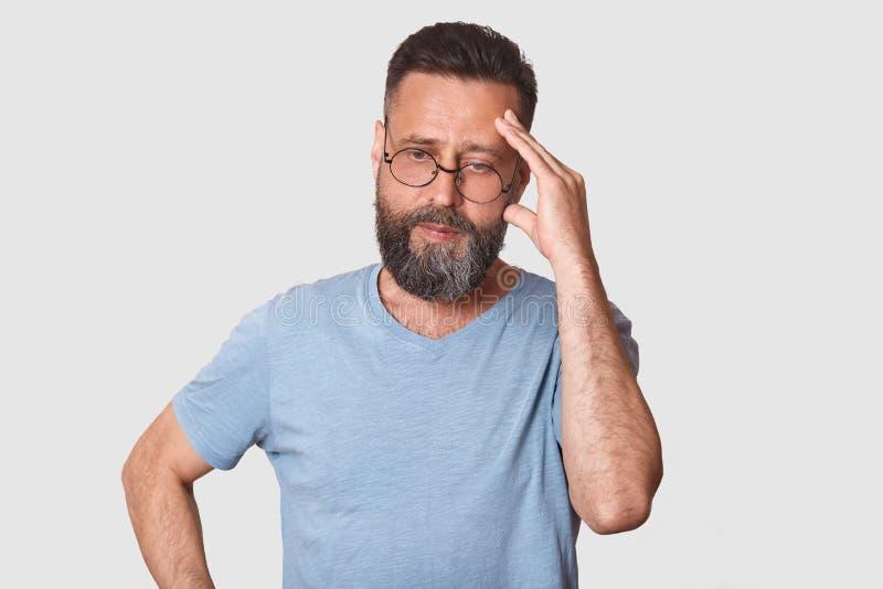 Portrait haut étroit d'homme âgé moyen bel Le mâle barbu en vêtements et verres gris pensant et regardant de côté, garde la main  image stock