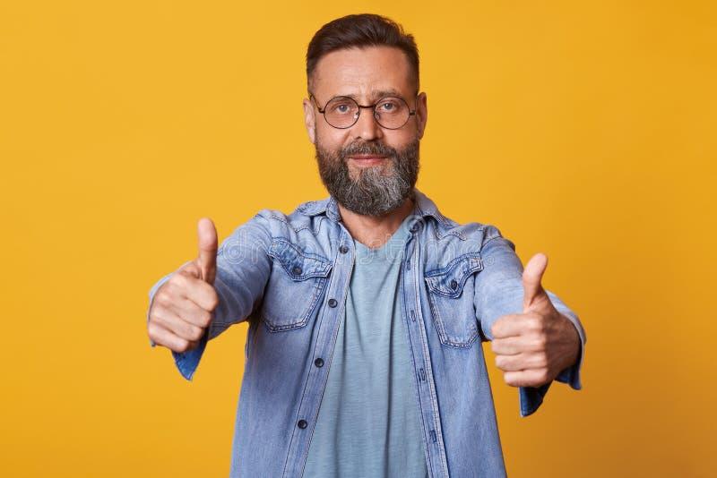 Portrait haut étroit d'homme barbu positif heureux dans la chemise de denim, le T-shirt gris et l'eyewear, montrant ses pouces et photos stock