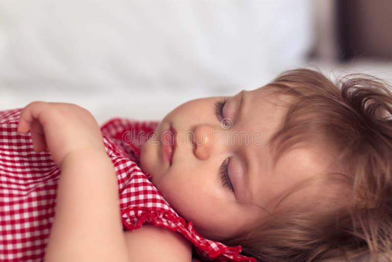 Portrait haut étroit d'un beau vieux bébé de neuf mois dormant sur le fond brouillé Visage d'enfant de sommeil mignon photos stock
