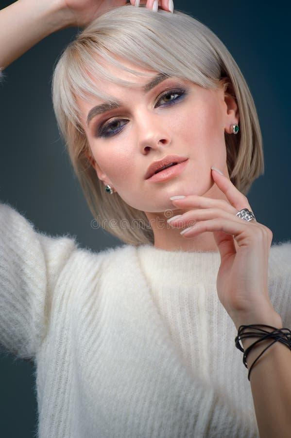 Portrait haut étroit d'une belle dame posant dans le studio sur le fond bleu image stock
