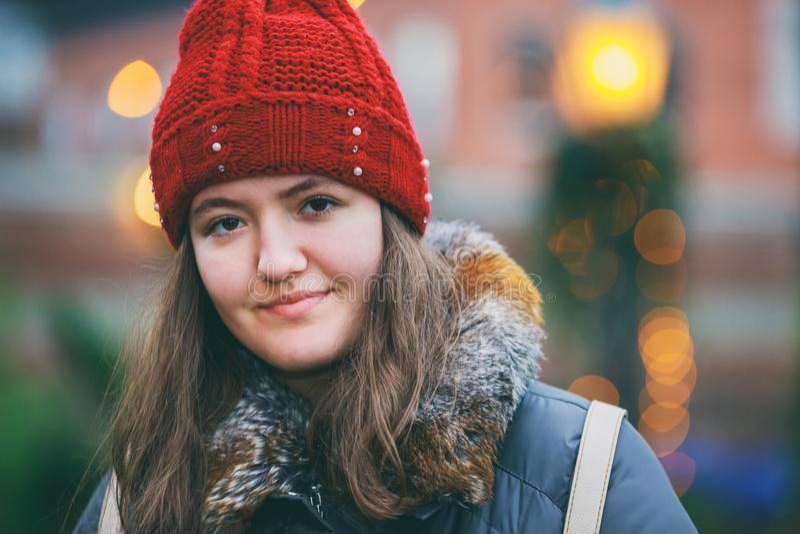 Portrait haut étroit d'une belle fille de sourire avec le bokeh coloré de lumières de cheveux bruns image libre de droits