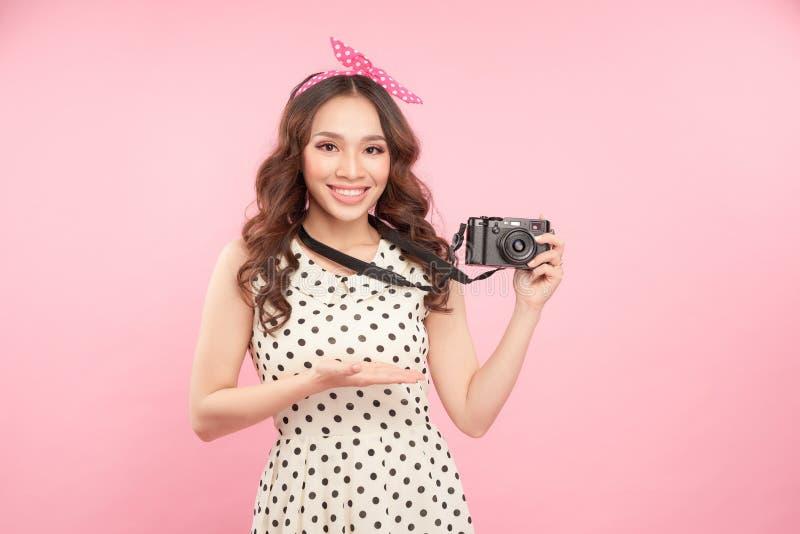 Portrait haut étroit d'une caméra de sourire de photo de participation de jeune fille d'isolement sur un fond rose images libres de droits