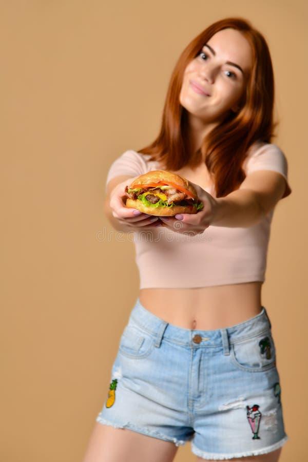 Portrait haut étroit d'une jeune femme affamée mangeant l'hamburger au-dessus du fond nu photo stock