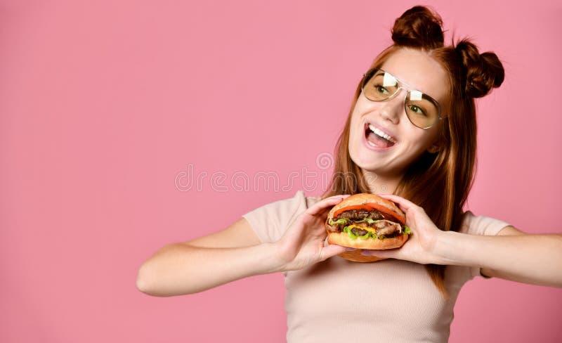 Portrait haut étroit d'une jeune femme affamée mangeant l'hamburger d'isolement au-dessus du fond blanc photos stock