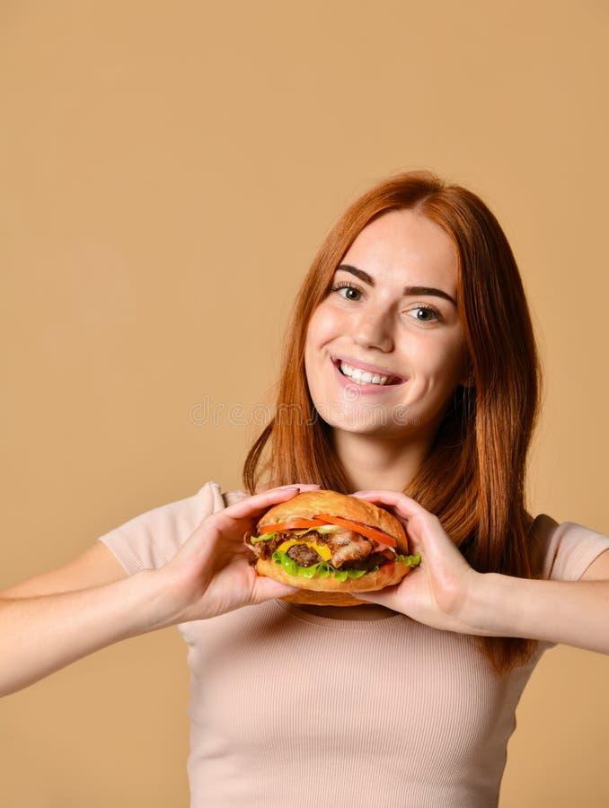 Portrait haut étroit d'une jeune femme affamée mangeant l'hamburger d'isolement au-dessus du fond nu photo libre de droits