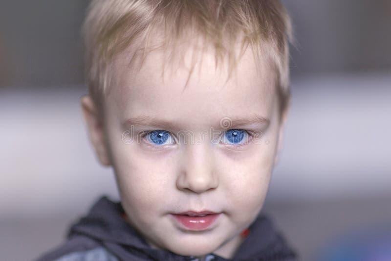 Portrait haut étroit de bébé garçon caucasien mignon avec l'expression très sérieuse de visage Yeux bleus lumineux, cheveux juste photos libres de droits