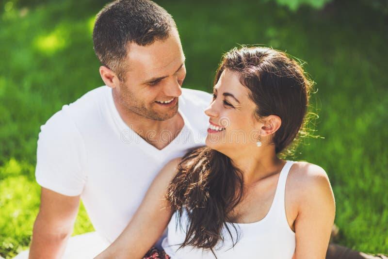 Portrait haut étroit de beaux couples dans l'amour se reposant sur une couverture de pique-nique extérieure Homme rêveur heureux  photos stock