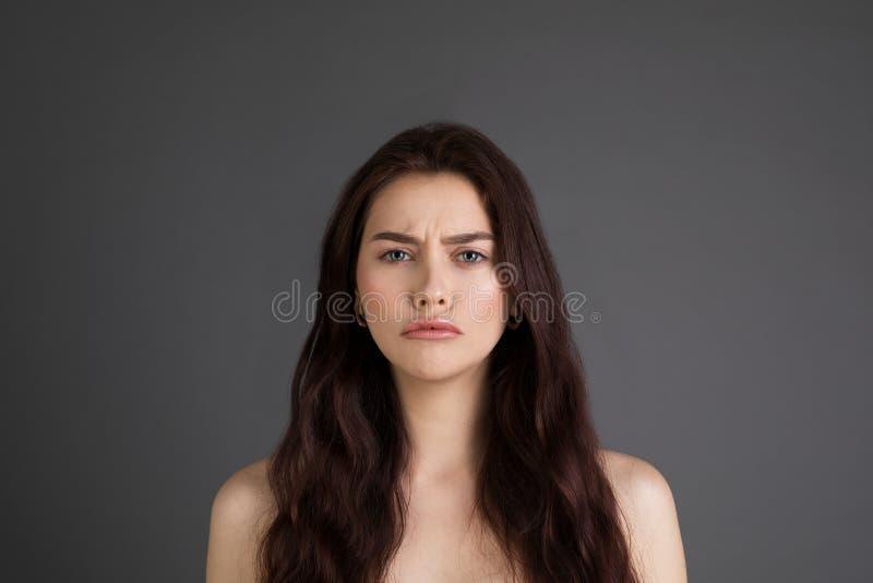 Portrait haut étroit de belle femme malheureuse offensée avec de longs cheveux de brune, épaules nues photographie stock