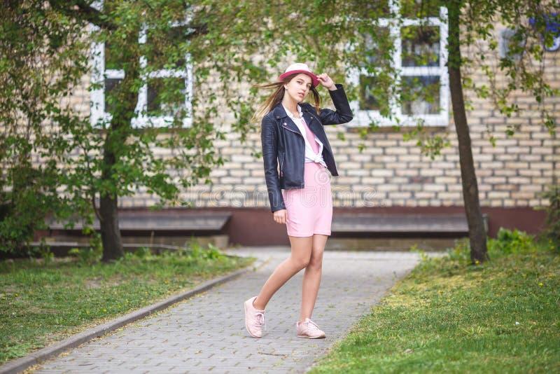 Portrait haut étroit de belle fille élégante d'enfant dans le chapeau près de l'immeuble de brique dans la rue urbaine comme fond photos stock