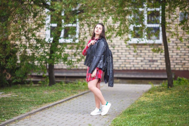 Portrait haut étroit de belle fille élégante d'enfant de grande taille plus avec la veste en cuir et la chemise de plaid rouge pr photographie stock