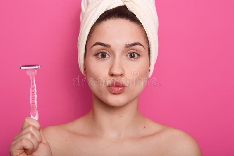 Portrait haut étroit de belle jeune femme maintenant ses lèvres pliées, tenant le rasoir pour raser, regardant directement la cam photographie stock
