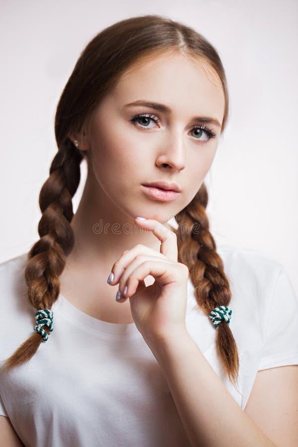 Portrait haut étroit de belle jeune fille sensuelle sur le fond blanc Femme attirante avec de longs cils et peau propre, tresses photo stock