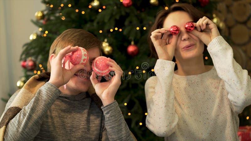 Portrait haut étroit de deux gais, couple positif tenant les jouets brillants ronds, couvrant des yeux, dupant autour sur décoré photos libres de droits