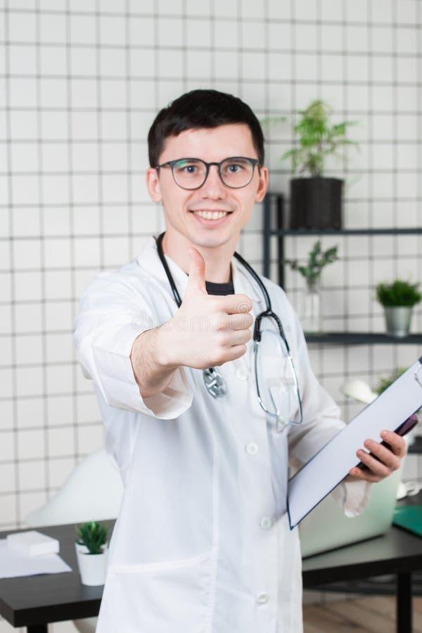 Portrait haut étroit de docteur de sourire recommandant la nouvelle manière du traitement en montrant le pouce  photo libre de droits