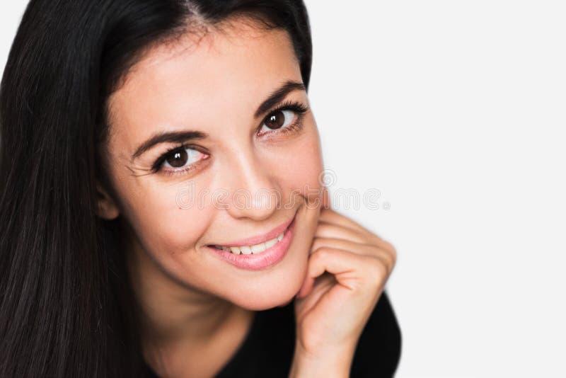 Portrait haut étroit de femme mignonne de brune avec le sourire de beauté, avec le visage de main Jeune jolie femme heureuse util photos stock