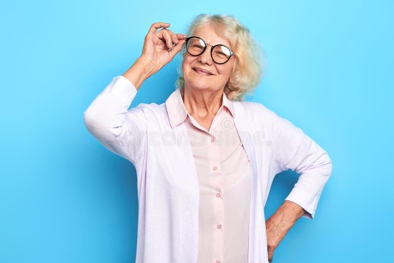 Portrait haut étroit de femme supérieure touchant ses verres images libres de droits