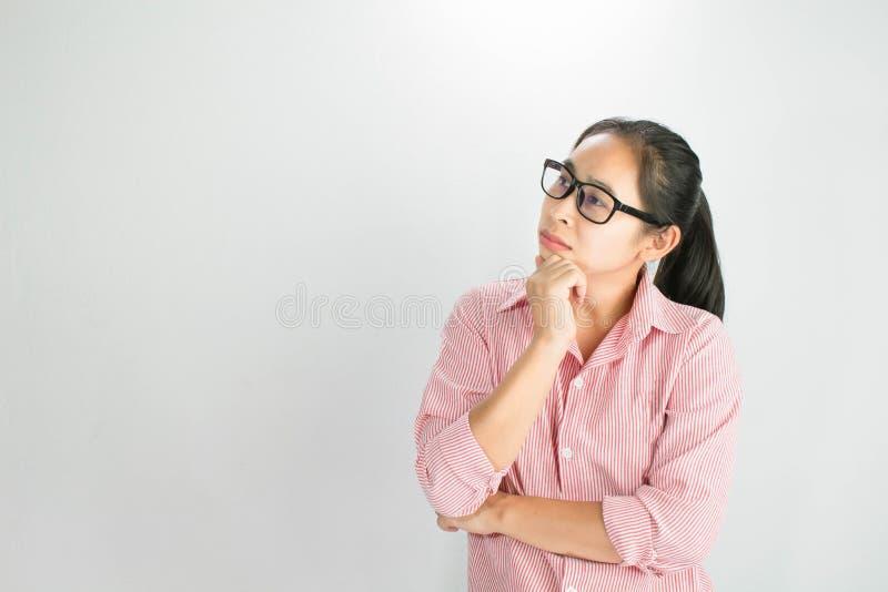 Portrait haut étroit de fille réfléchie de femme asiatique, verres de port et main de se tenir près du visage, regardant sérieuse image stock