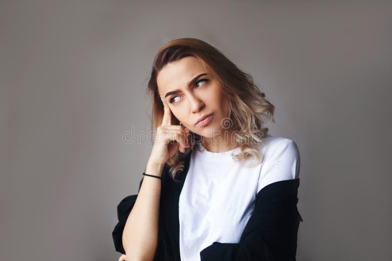 Portrait haut étroit de fille réfléchie sûre blonde bouclée, tenant la main près du visage photos stock