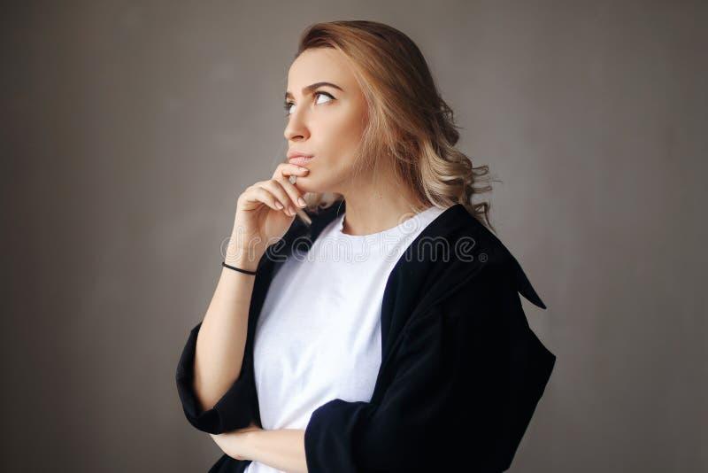 Portrait haut étroit de fille réfléchie sûre blonde bouclée, tenant la main près du visage photo libre de droits