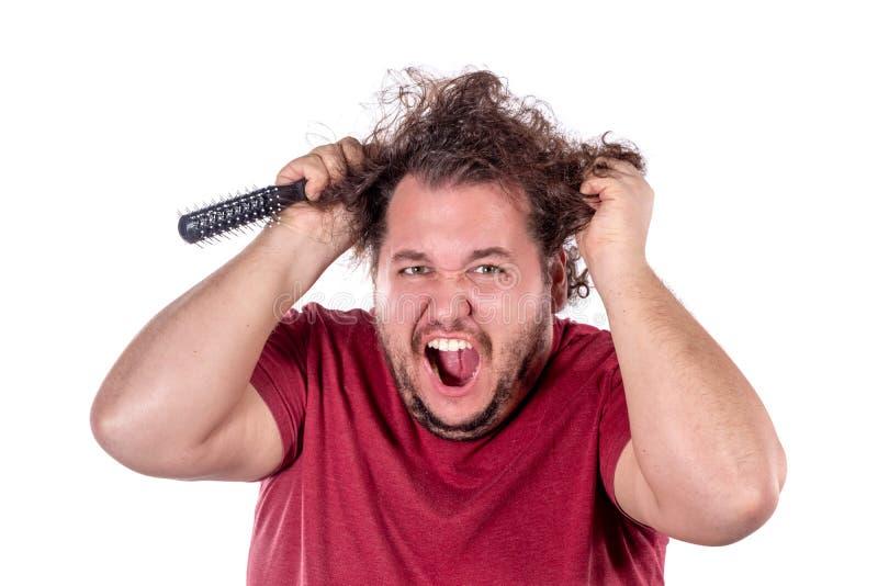 Portrait haut étroit de gros essais d'homme pour se peigner les cheveux embrouillés et vilains avec un petit peigne noir d'isolem image libre de droits