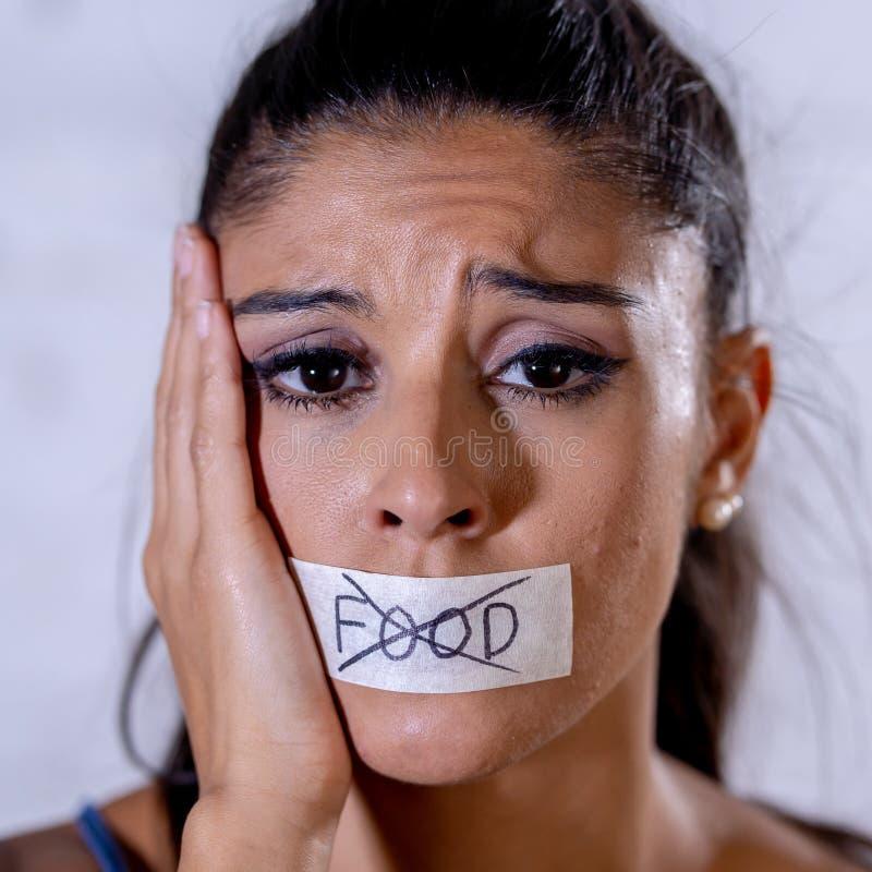Portrait haut étroit de jeune femme latine attirante avec la bouche scellée sur bande de bâton avec le texte aucune nourriture da photo stock
