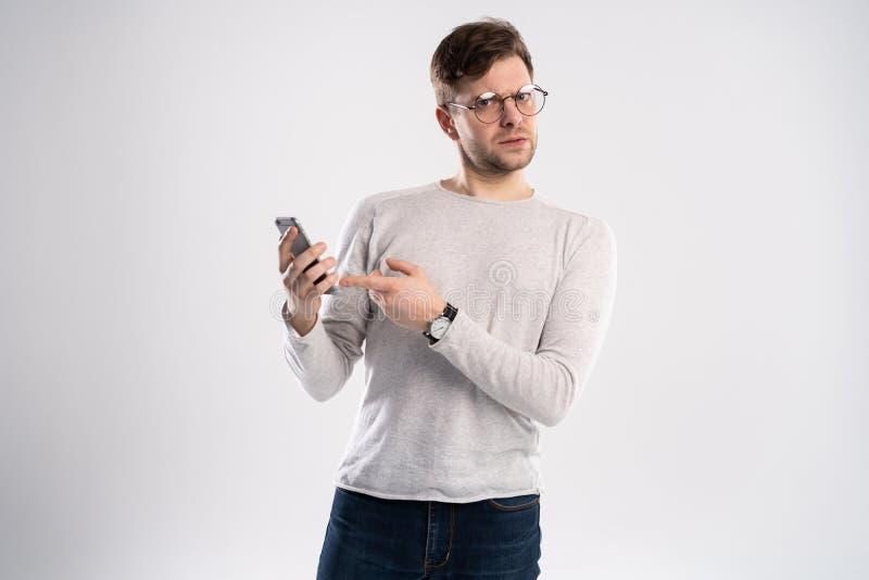 Portrait haut étroit de jeune homme beau dans le T-shirt, le smartphone blancs de participation, semblant texte effrayé et confus photos stock