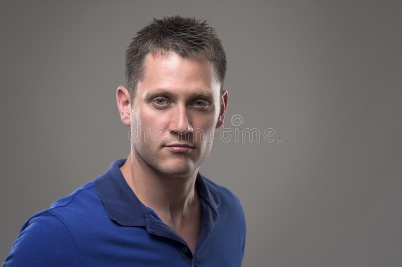Portrait haut étroit de jeune homme méfiant avec le regard fixe intense à la caméra images libres de droits