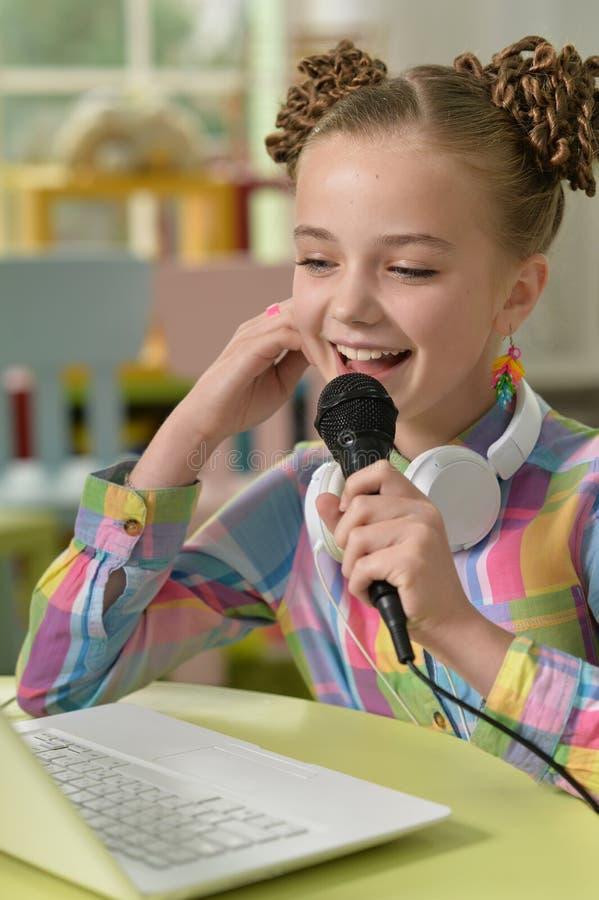 Portrait haut étroit de karaoke mignon de chant de petite fille avec l'ordinateur portable à sa pièce image stock
