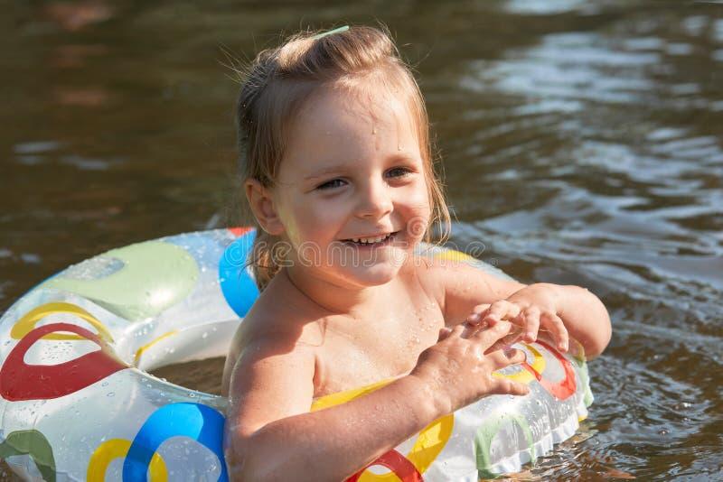 Portrait haut étroit de l'enfant drôle adorable regardant de côté, souriant sincèrement, ayant l'expression du visage agréable, p photos libres de droits