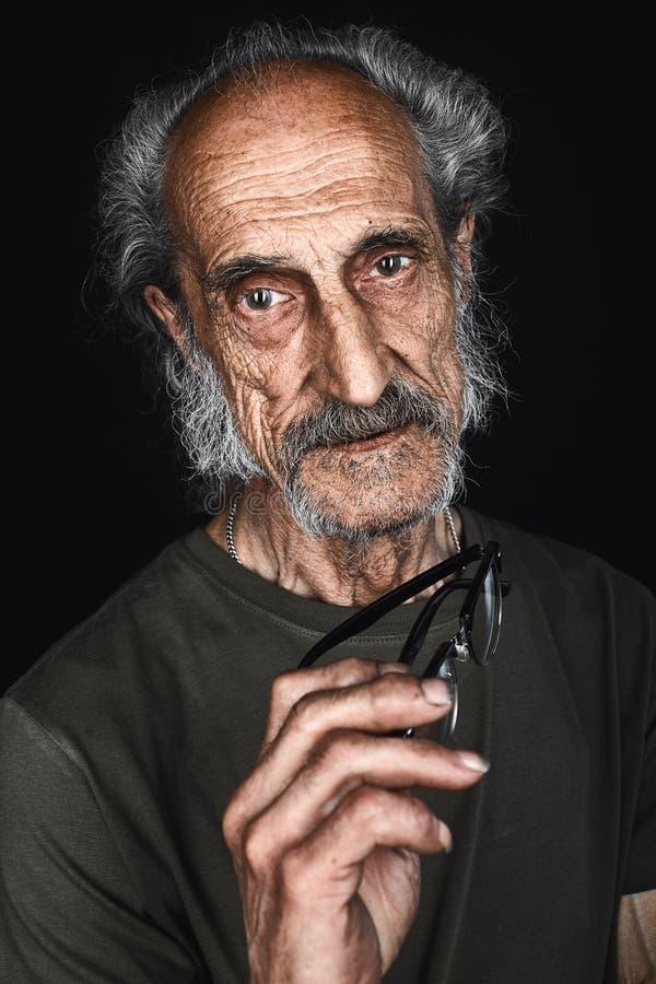 Portrait haut étroit de l'homme supérieur en verres enlevant des verres photo stock