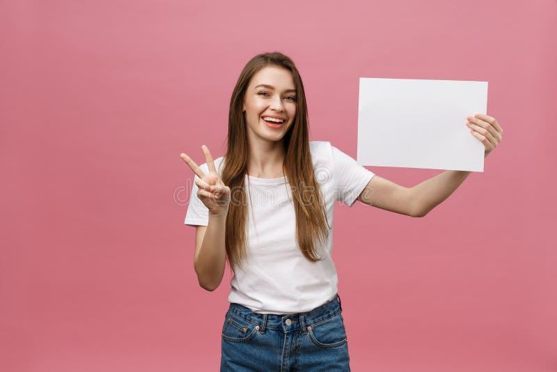 Portrait haut étroit de la femme riante positive souriant et jugeant la grande affiche blanche de maquette d'isolement sur le fon photo stock