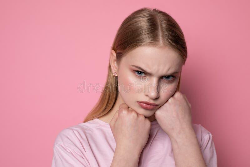Portrait haut ?troit de la jeune belle fille f?ch?e soumise ? une contrainte tenant des poings sur le visage photographie stock