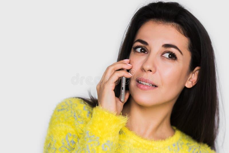 Portrait haut étroit de la jeune femme attirante sérieuse à l'aide du téléphone intelligent au-dessus du fond gris-clair photos stock