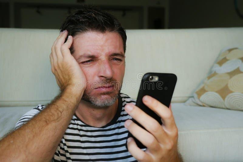 Portrait haut étroit de visage de jeune homme attirant et soumis à une contrainte utilisant le téléphone portable fatigué et malh image libre de droits