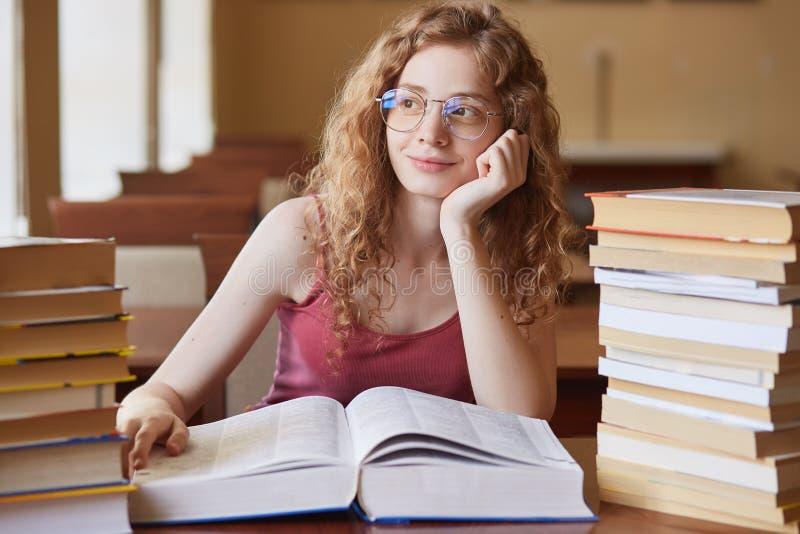 Portrait haut étroit des cheveux bouclés roux d'étudiant de wirh attrayant réfléchi de fille, en verres se reposant parmi différe photo stock