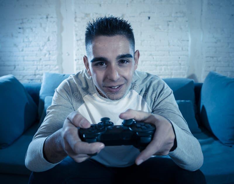 Portrait haut étroit du jeune homme dépendant jouant le jeu vidéo la nuit dans le concept de jeu et de dépendance photo stock