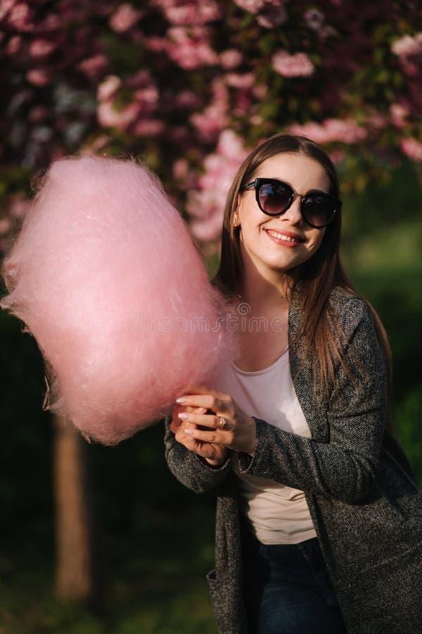 Portrait haut ?troit de fille de sourire tenant la sucrerie de coton dans des mains Fille habill?e dans le blazer et des lunettes image libre de droits