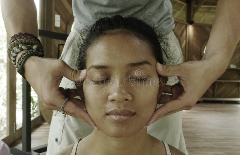 Portrait haut ?troit de visage de la jeune femme indon?sienne asiatique magnifique et d?contract?e recevant le massage tha?landai photos stock