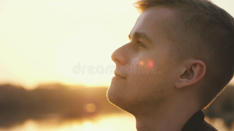 Portrait haut ?troit du jeune homme beau songeur regardant appr?ciant la nature dans des rayons du soleil le coucher du soleil image stock